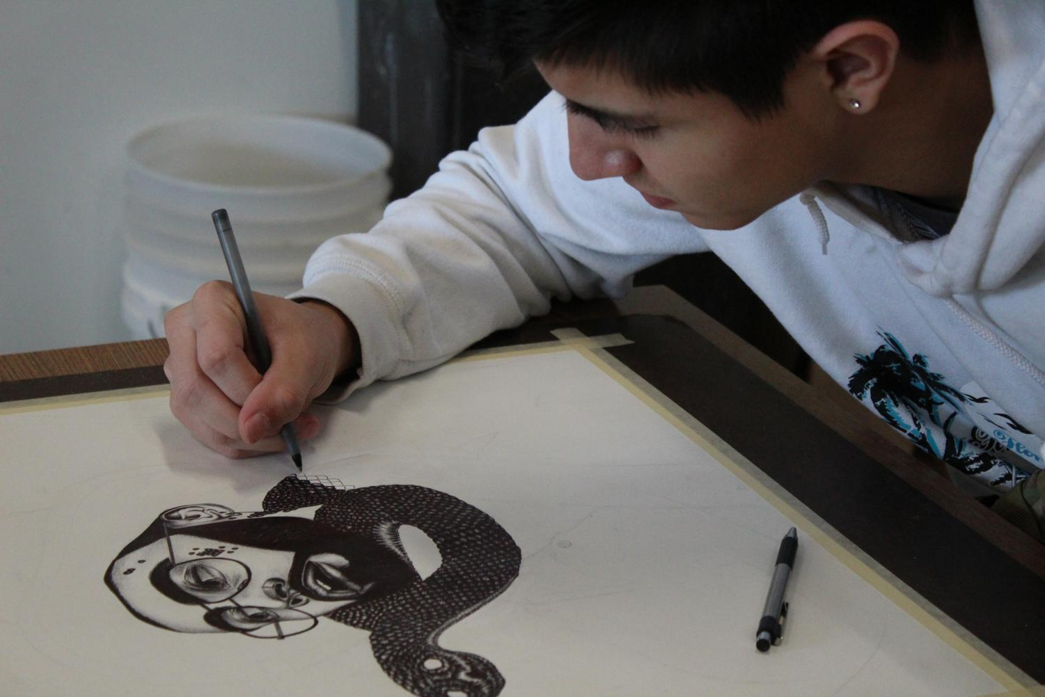 Robert Fuentes working on his drawing.