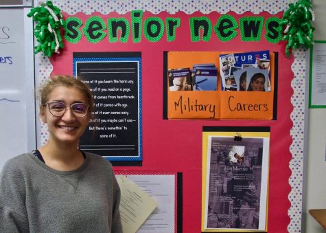 Crystal Carrillo next to the senior news board.