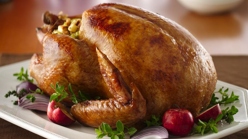 A golden brown turkey sits on a plate.