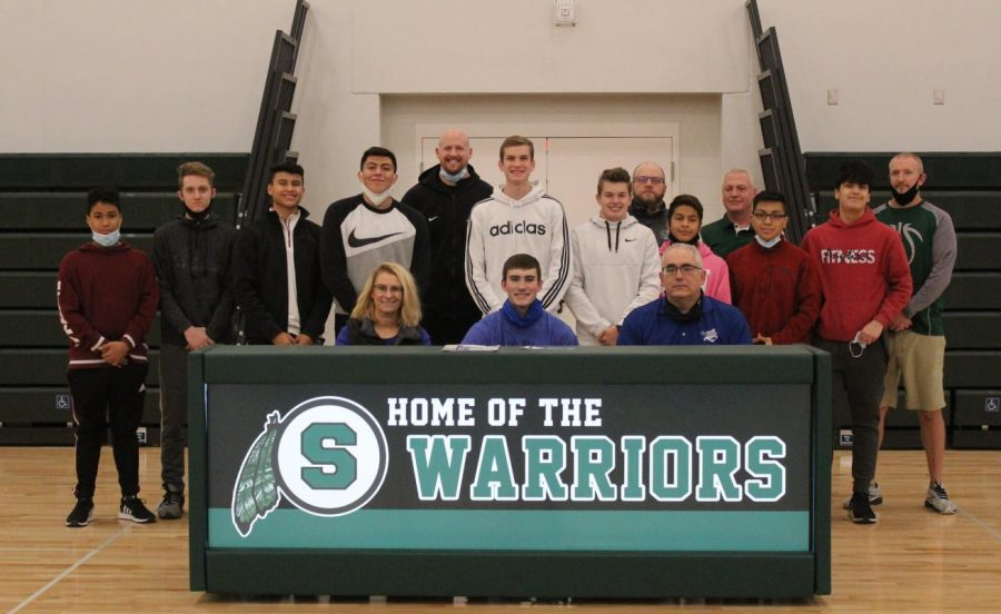 Easton Hall with his parents and basketball team members pose for photo at the signing.