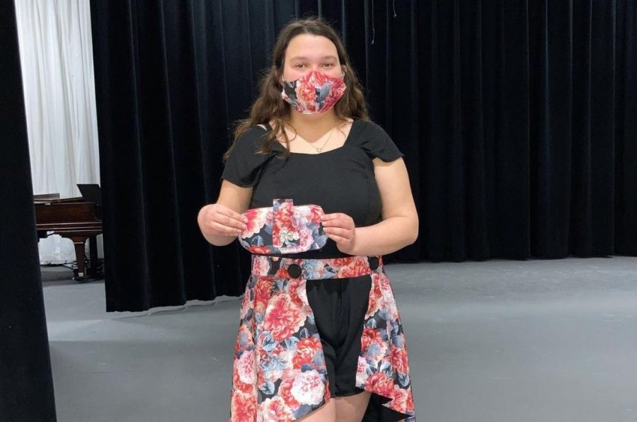Vivi Sayer shows off her handmade outfit, including a mask and clutch purse.