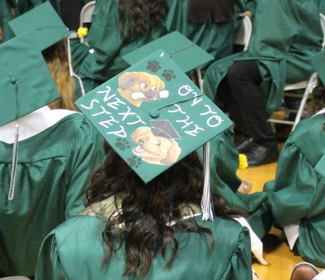 """A Graduating Senior wears her cap with a design reading """"On to the next step""""."""